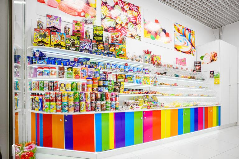 яркая витрина с открытыми полками и шкафчиками на замках для магазина сладостей